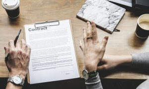 a person looking at a contract with a lawyer