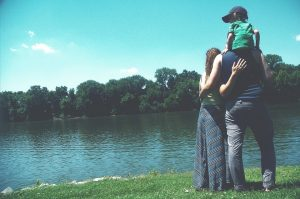 a family of three by the river