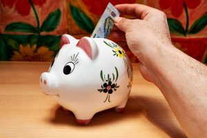 a hand putting cash into a piggy bank and saving money for Movers Cary NC