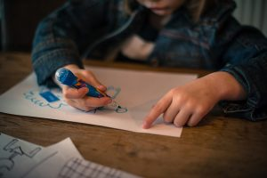 Kid is drawing on blank paper