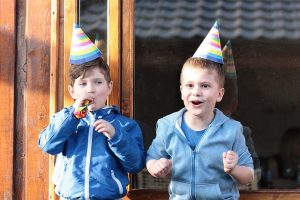 Two boys with party hats having fun
