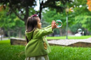 a girl playing with a soap bubble