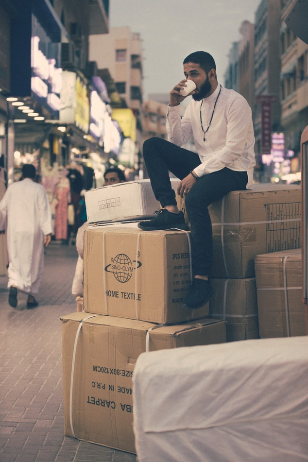 A men sitting on boxes drinking coffee
