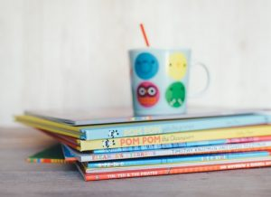 several colorful books and a cup
