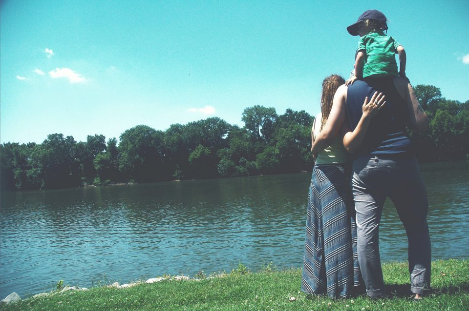 Image of a family standing on a lake shore