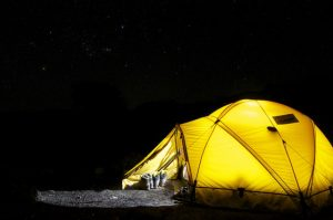 A yellow tent under a starry night