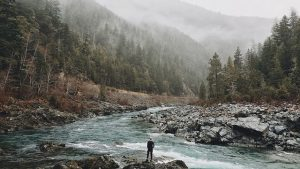 A man standing on a mountain river shoring, mesmerizing at nature's beauty