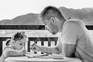 A black and white photo of a girl drawing with her dad.