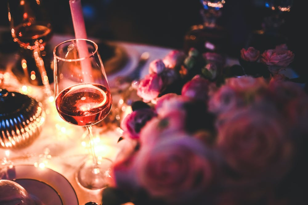 Wine glass with rose wine and roses perfect for a date night in one of the Best cities for singles in NC
