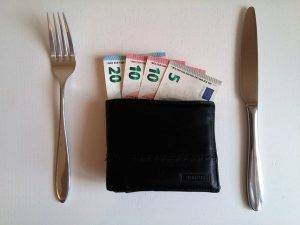 Wallet full of money with a fork on the left and a knife on the right asks the questions how much should you tip your movers