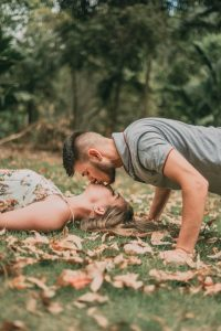 A couple kissing laying on the grass