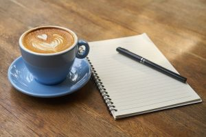 Coffee cup, an empty notebook and a pen