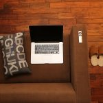 Couch, laptop and a pillow where you can read our tips on how to settle into a new neighborhood