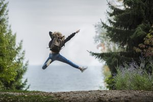 An explorer girl jumping with joy