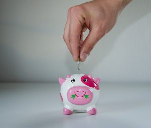 A person putting a coin in a piggy bank