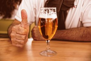A man giving a thumbs up next to a glass of beer