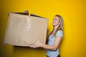 A girl with a cardboard packing box
