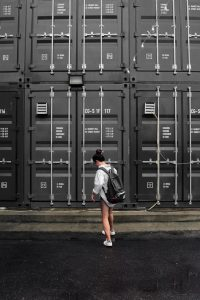 A girl standing in front of storage containers thinking about which one to choose